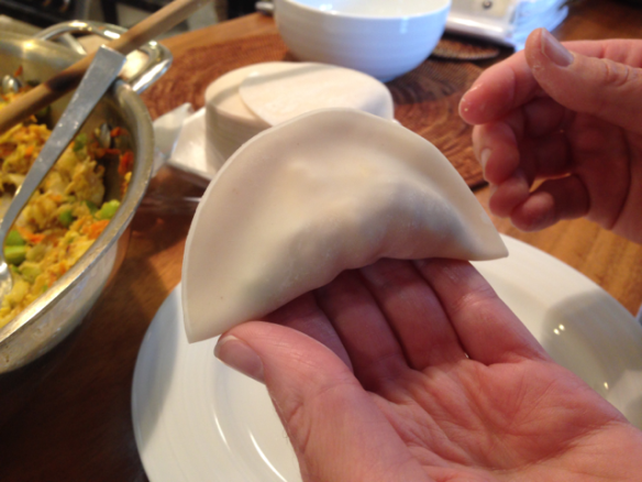 Now fold the dumpling in half to make a crescent shape and pinch the edges together.