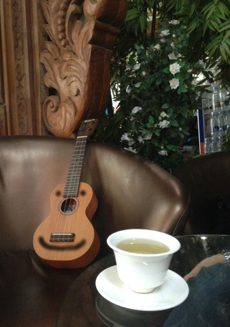 The ukulele enjoys a sip of tea while sitting in the comfy chair. (This comfy chair just so happens to be in Yangon domestic terminal).