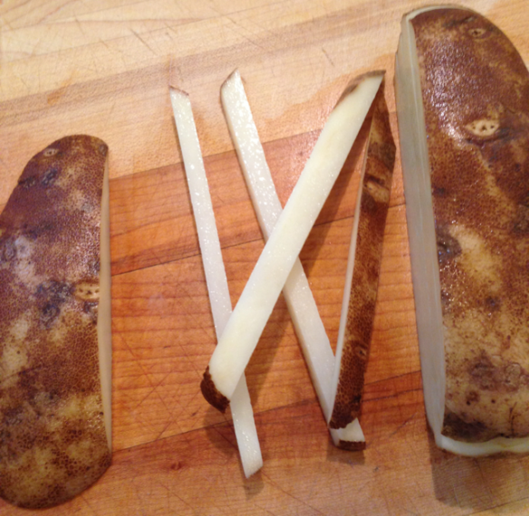 Cut 1/4 inch off of one side of the potato, then roll the potato onto the flat side. Cut the remaining potato into 1/4 inch planks, stack the planks and cut them into 1/4 inch fries.